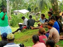 Talking to villagers during public awareness campaign